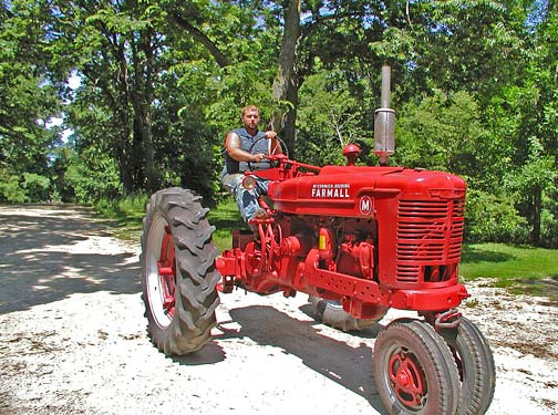 Ben Johnson on his shiny red restored Farmall M tractor
